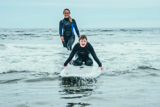 girl with downs syndrome learning to surf in rhode island, USA