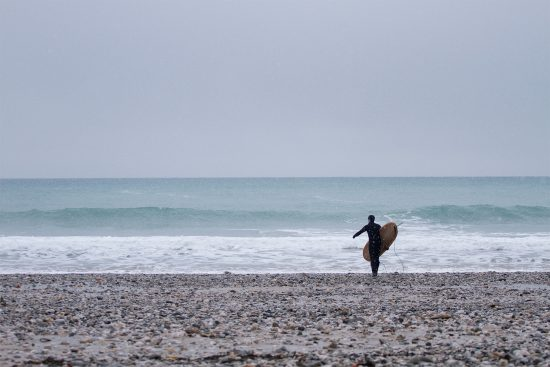 surfer walking in the snow towards the sea