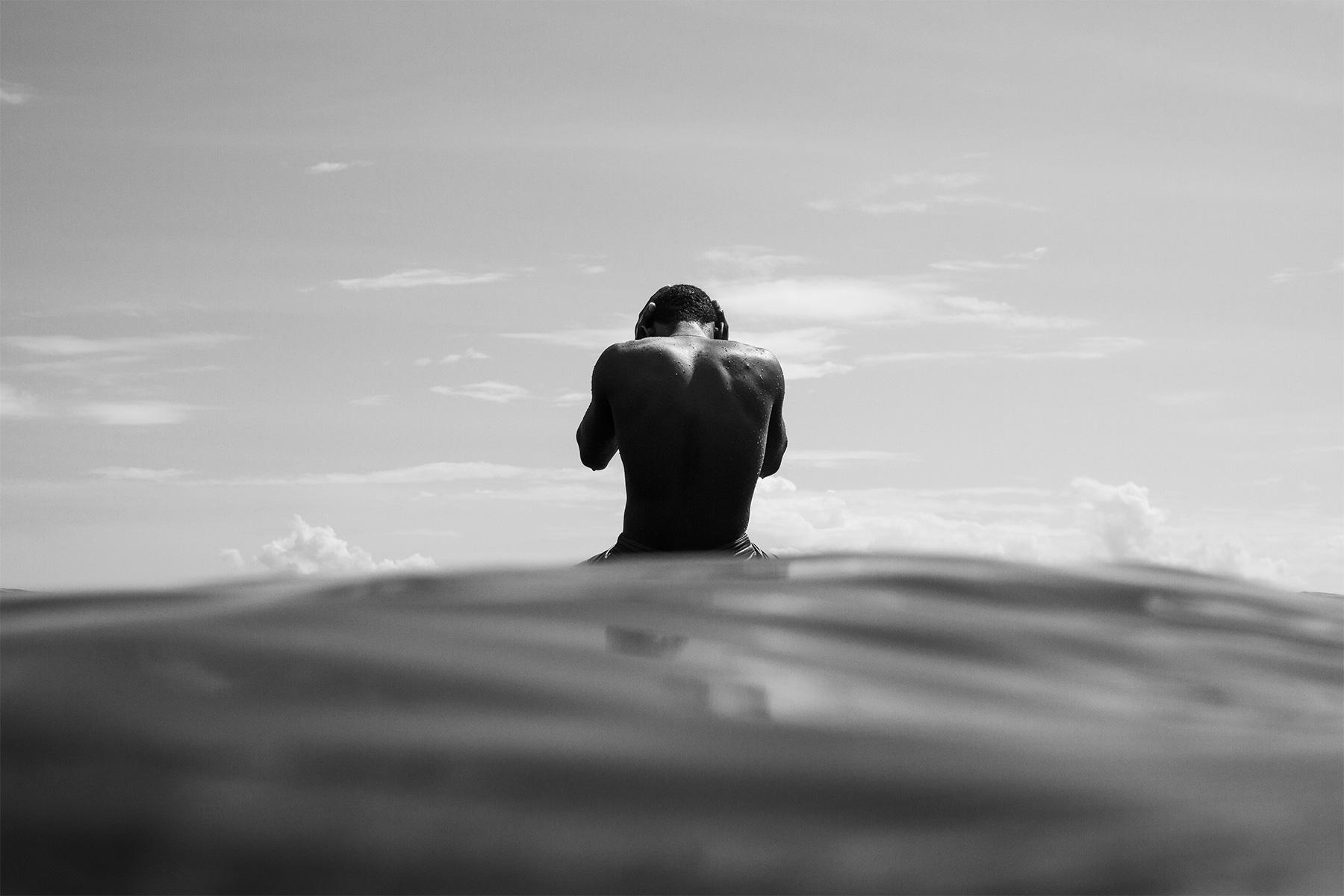 black and white photograph of a surfer sat waiting for a wave with his head in his hands, by joel sharpe
