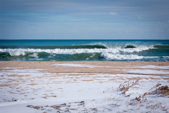 breaking waves on a snow covered beach on the black sea in romania