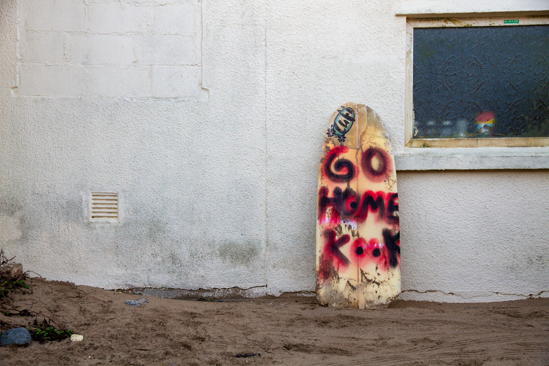 """broken surfboard with """"go home kook"""" localism graffiti spray painted on it leaning against a wall at the beach"""