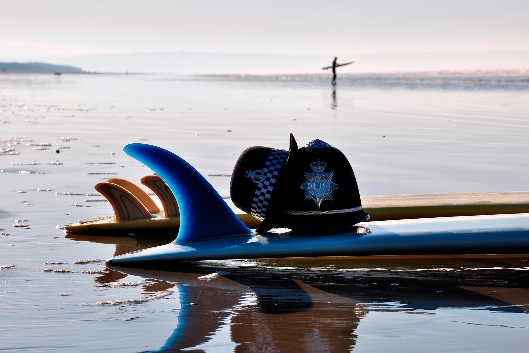 a british police hat and helmet on a surfboard on the beach