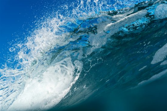 underneath the lip of a crystal clear breaking wave photographed by mat arney