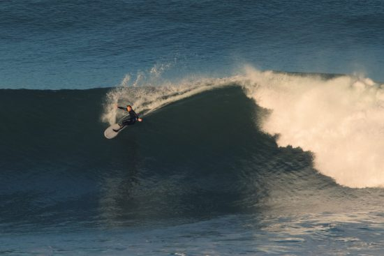surfer torren martyn doing a cutback on a big wave in morocco, photographed by ishka folkwell